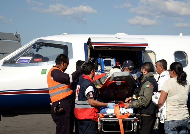 A child injured in the explosion of the fireworks market in Tultepec, a suburb of Mexico City, is transferred to an ambulance in Toluca, the capital of Mexico state, to be taken to a hospital in Galveston, Texas in the United States on December 21, 2016.