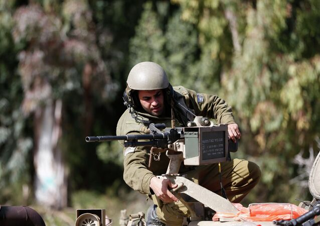 An Israeli soldier adjusts a weapon atop an armoured military ambulance near Israel's border with Lebanon