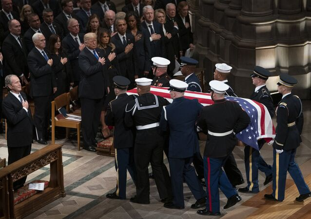 The flag-draped casket of former President George H.W. Bush is carried by a military honor guard
