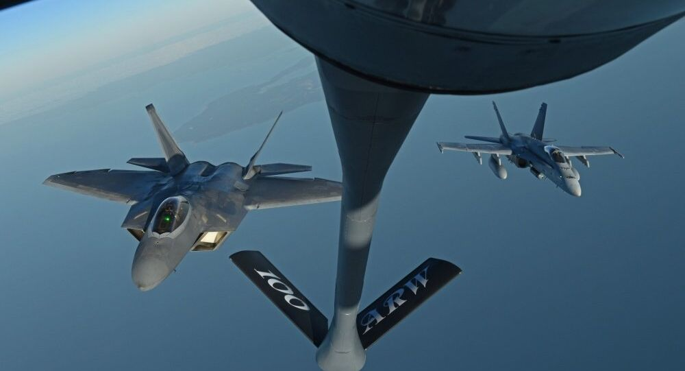 A U.S. Air Force F-22 Raptor and a Finnish air force F/A-18 Hornet fly behind a U.S. Air Force KC-135 Stratotanker during training off the coast of Finland, 19 October 2018.