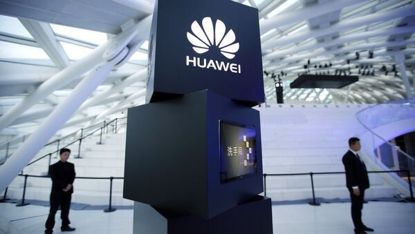 Security personnel stand near a pillar with the Huawei logo - Sputnik International