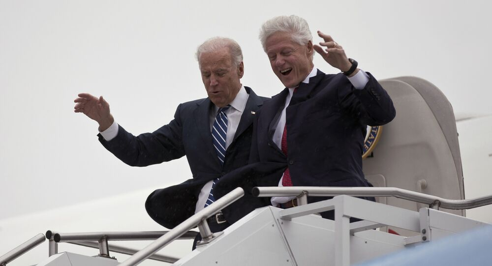 Vice President Joe Biden, left, accompanied by former President Bill Clinton walk carefully off Air Force Two during a rainstorm,, upon their arrival in Youngstown, Ohio, for a campaign stop, Monday, Oct. 29, 2012.