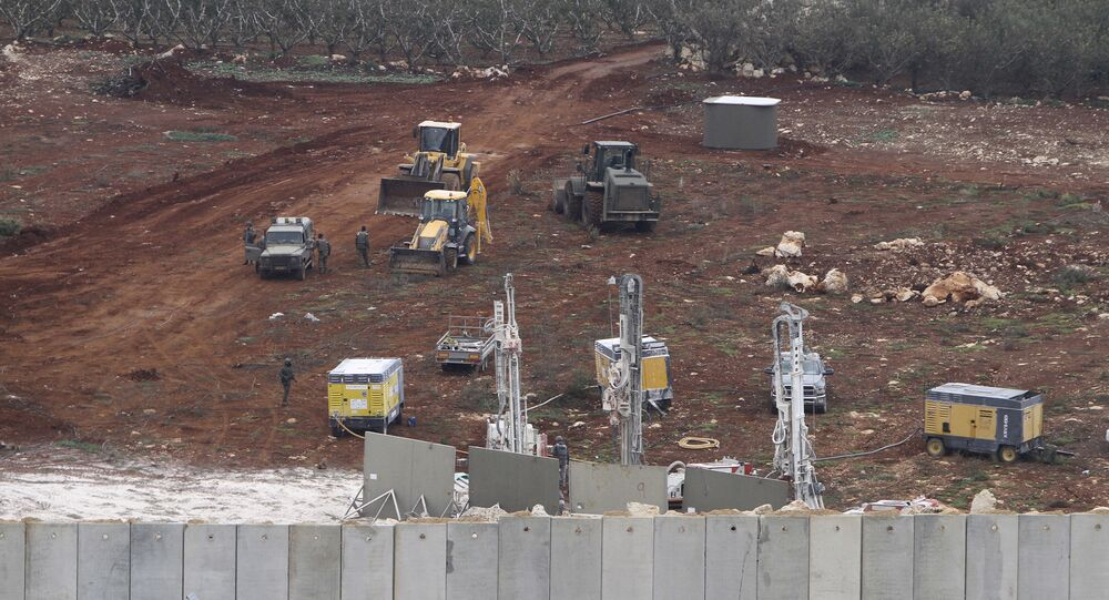 An Israeli military digger works on the Lebanese-Israeli border next to a wall that was built by Israel in the southern village of Kafr Kila, Lebanon, Tuesday, Dec. 4, 2018.