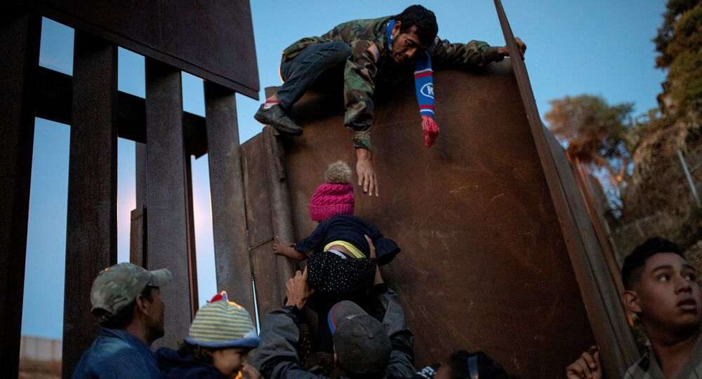 Migrants from Honduras, part of a caravan of thousands from Central America trying to reach the United States, try to jump a border fence to cross illegally from Mexico to the U.S, in Tijuana, Mexico, December 2, 2018