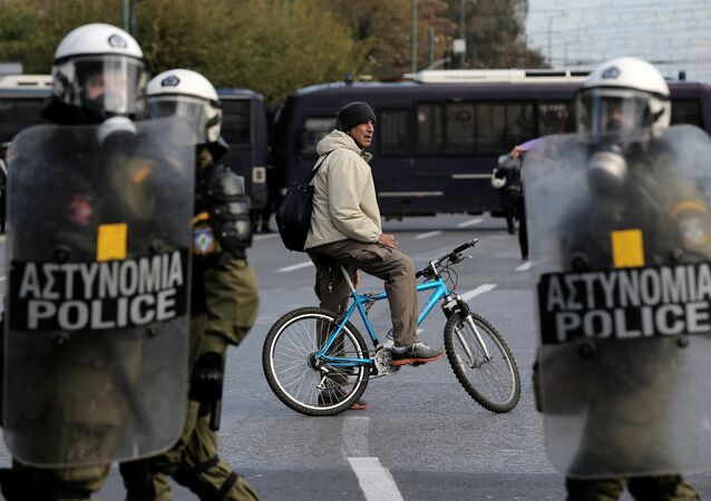 A man on a bike stands behind a police cordon guarding an anniversary rally marking the 2008 police shooting of 15-year-old student, Alexandros Grigoropoulos, in Athens