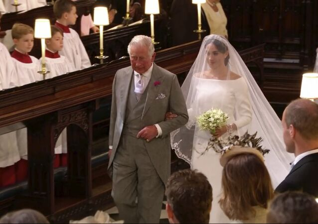 In this frame from video, Meghan Markle walks down the aisle with Prince Charles for her wedding ceremony at St. George's Chapel in Windsor Castle in Windsor, near London, England, Saturday, May 19, 2018.