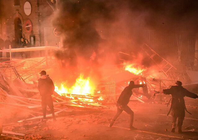 Protestors throw projectiles in a burning barricade during a demonstration of yellow vests (gilets jaunes) against rising costs of living they blame on high taxes in Toulouse, southern France, on December 8, 2018