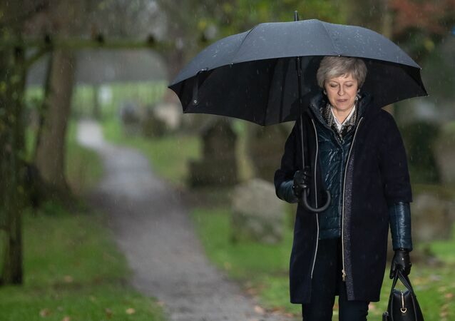 Britain's Prime Minister Theresa May shelters from the rain under an umbrella after attending a church service near to her Maidenhead constituency, west of London on December 9, 2018