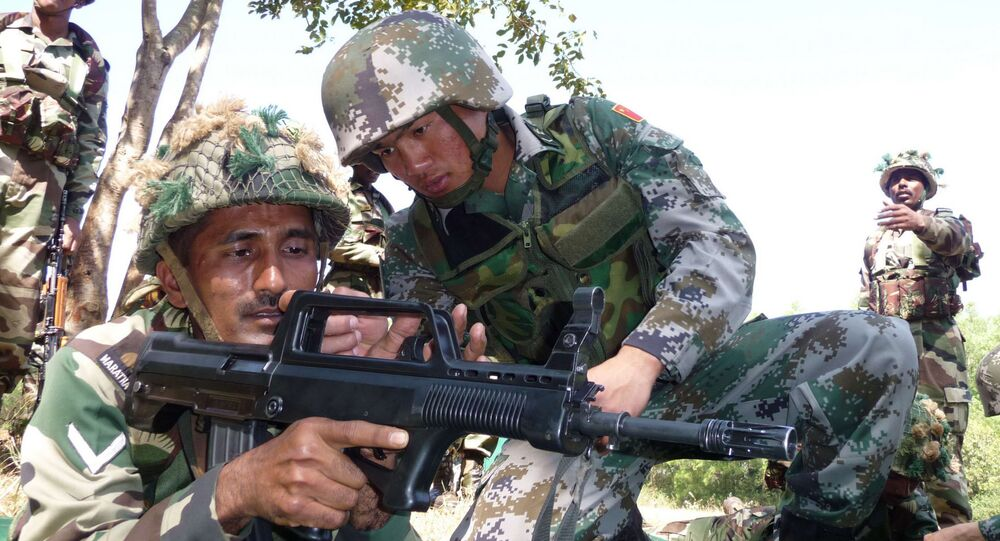 Indian soldier, left, tries a Chinese weapon during a training session (File)