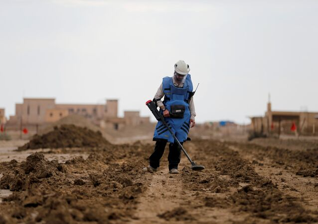 A man holds a device to detect mines in an area recently cleared of mines and unexploded ordnance in a project to clear the area near Qasr Al-Yahud, a traditional baptism site along the Jordan River, near Jericho in the occupied West Bank, December 9, 2018