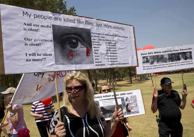 White South Africans hold placards during a protest against the violent murder of farmers which they term genocide and oppressive state policies in favour of blacks in Pretoria on October 10, 2013