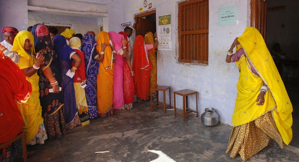 Indian women wait in a queue to cast their votes in village Padampura, near Ajmer, India, Friday, Dec. 7, 2018