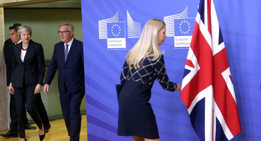 A staff member adjusts the British flag as British Prime Minister Theresa May and European Commission President Jean-Claude Juncker arrive at the EC headquarters in Brussels, Belgium November 21, 2018