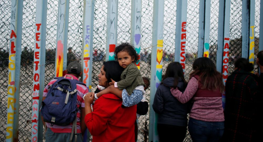 A woman carries her son as she looks at people taking part in a gathering in support of the migrant caravan in San Diego, U.S., close to the border wall between the United States and Mexico, in Tijuana, Mexico December 10, 2018