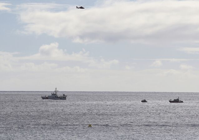A U.S. Coast Guard helicopter flies over rescue boats at the scene of plane crash off Honolulu, Wednesday, Dec. 12, 2018