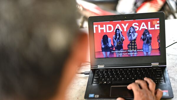 A man watches a commercial featuring K-pop supergroup Blackpink on his laptop in Jakarta on December 12, 2018, after the advertisement was banned by the Indonesian Broadcasting Commission. - Sputnik International