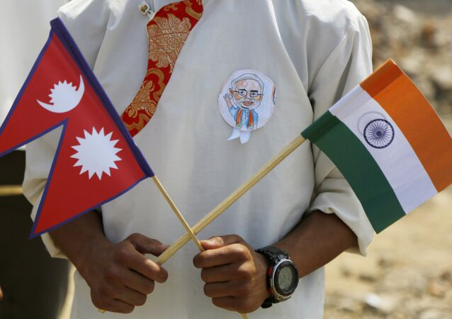A school student holds a Nepalese and Indian flag and wears a badge with a portrait of Indian Prime Minister Narendra Modi as he waits to welcome Modi in Kathmandu, Nepal, Friday, May 11, 2018
