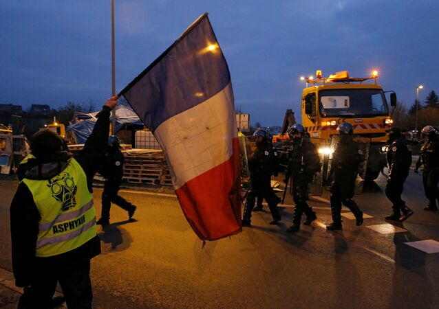 A protester wearing a yellow vests holds a French flag as police arrive to secure the site as their shelter at a traffic island is dismantled near the A2 Paris-Brussels motorway in Fontaine-Notre-Dame, France, December 14, 2018