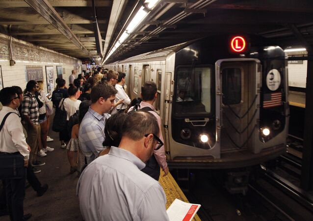 Commuters wait on a platform as the L subway train arrives in the 1st Avenue station.