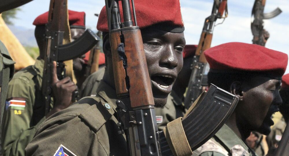 In this photo taken Thursday, April 14, 2016, government soldiers follow orders to raise their guns during a military parade in Juba, South Sudan