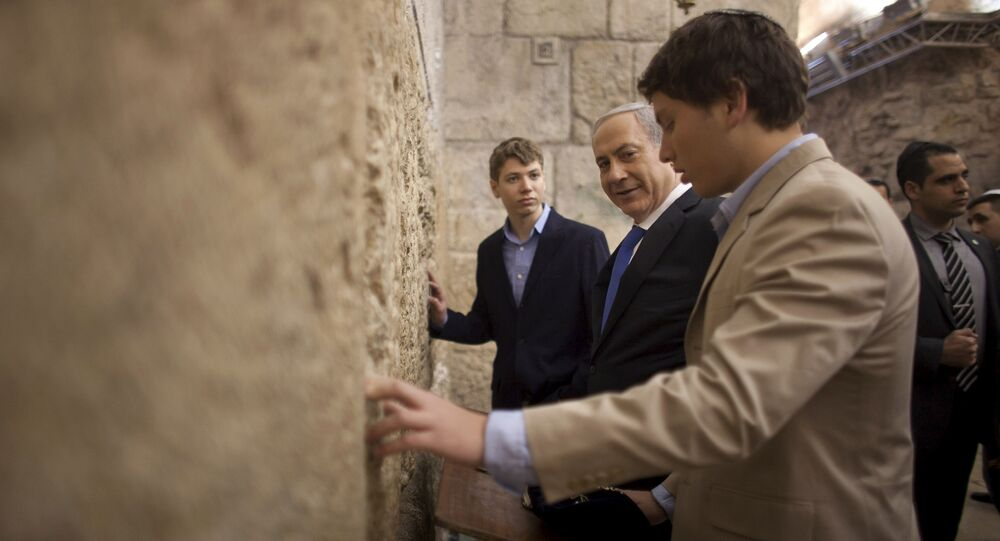 In this Jan. 22, 2013 file photo, Israeli Prime Minister Benjamin Netanyahu, center, prays with his sons Yair, background, and Avner, right, at the Western Wall, the holiest site where Jews can pray, in Jerusalem's Old City. Israeli political leaders are lashing out at Prime Minister Benjamin Netanyahu's eldest son for posting an anti-Semitic caricature aimed at his father's critics