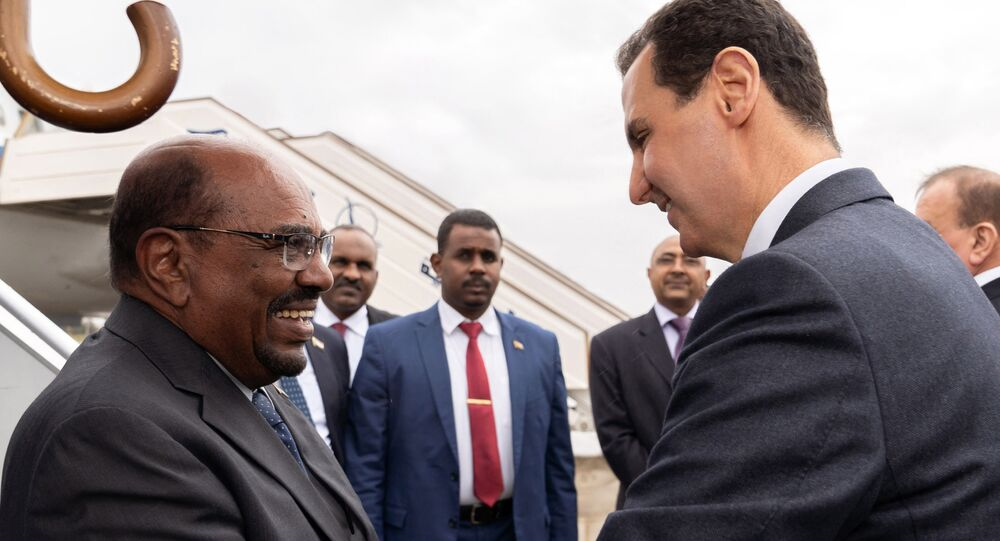 In this photo released by the Syrian official news agency SANA, Syrian President Bashar Assad, right, shakes hands with Sudan's President Omar al-Bashir in Damascus, Syria, Sunday, Dec. 16, 2018.