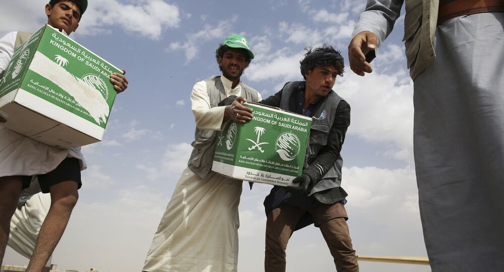 In this Saturday, Feb. 3, 2018 photograph, relief workers unload aid carried into Yemen by the Saudi military in Marib, Yemen