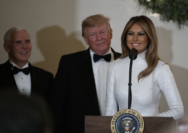 First lady Melania Trump, opined by President Donald Trump, and Vice President Mike Pence pauses as she speaks during the Congressional Ball in the Grand Foyer of the White House in Washington, Saturday, Dec. 15, 2018