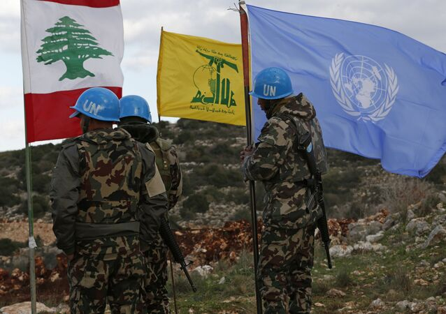 In this Thursday, Dec. 13, 2018 photo, UN peacekeepers hold their flag while standing next to Hezbollah and Lebanese flags, at the site where Israeli excavators are working, near the southern border village of Mays al-Jabal, Lebanon