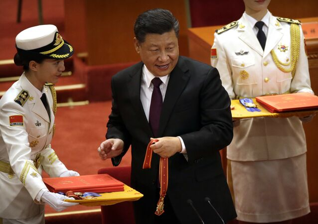 Chinese President Xi Jinping prepares to present a medallion during a conference to commemorate the 40th anniversary of China's Reform and Opening Up policy at the Great Hall of the People in Beijing, Tuesday, Dec. 18, 2018