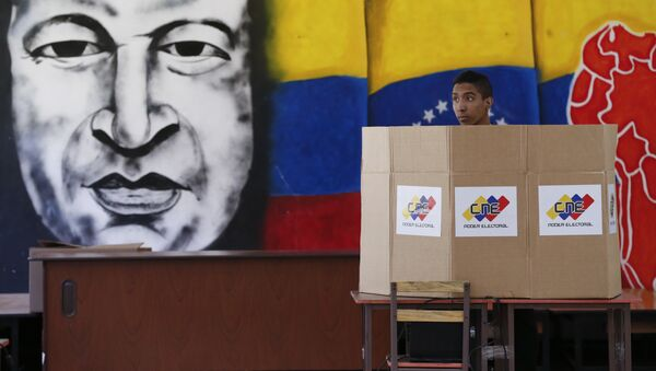 A voter chooses his candidate next to a mural of late Venezuelan President Hugo Chavez during presidential elections in Caracas, Venezuela - Sputnik International