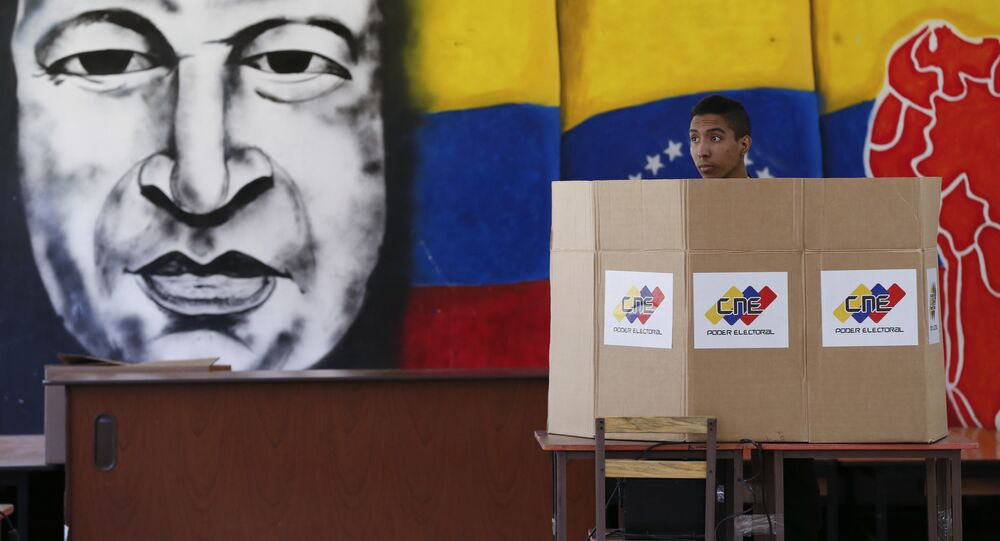 A voter chooses his candidate next to a mural of late Venezuelan President Hugo Chavez during presidential elections in Caracas, Venezuela