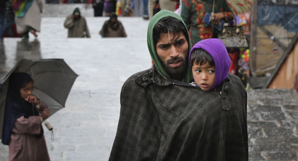 A Kashmiri man covers his son under his robe, locally known as phiran, from cold weather in Srinagar, Indian controlled Kashmir, Thursday, March 17, 2016
