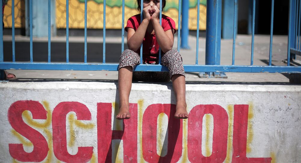 In this Monday, July 14, 2014 photo, a Palestinian girl sits on the wall of the New Gaza United Nations School, where dozens of families have sought refuge after fleeing their home in fear of Israeli airstrikes