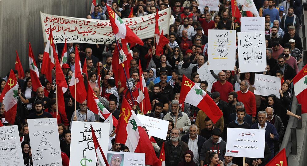 Anti-government demonstrators hold banners during a march organized by the country's communist party, in Beirut, Lebanon, Sunday, Dec. 16, 2018.