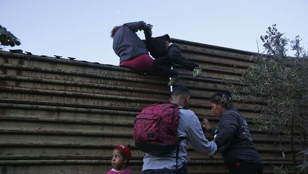 Honduran migrants help each other to cross over the U.S. border wall to San Diego, California, from Tijuana, Mexico, Saturday, Dec. 15, 2018 - Sputnik International