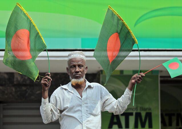 A Bangladeshi man waves national flags