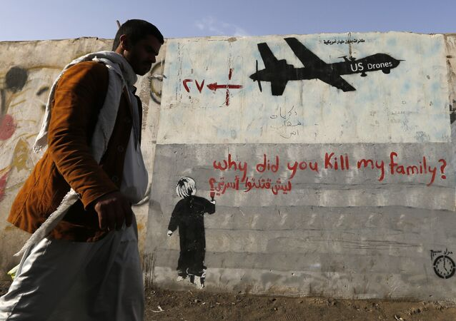 A man walks past a graffiti, denouncing strikes by U.S. drones in Yemen, painted on a wall in Sanaa, Yemen on November 13, 2014