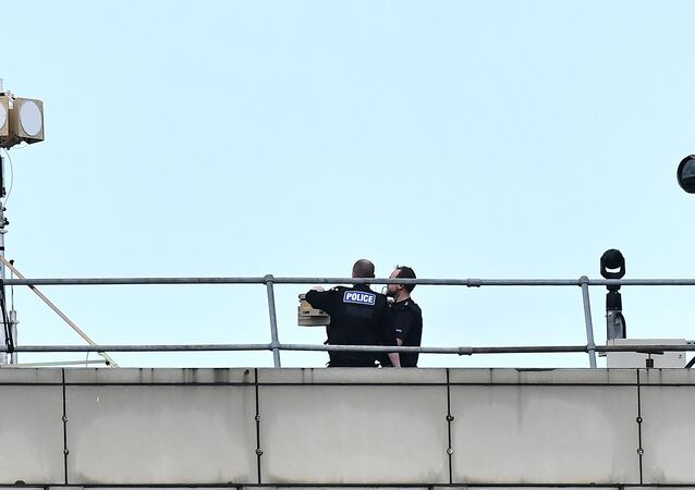 Police officers stand near equipment on the rooftop of a building at London Gatwick Airport, south of London, on December 21, 2018