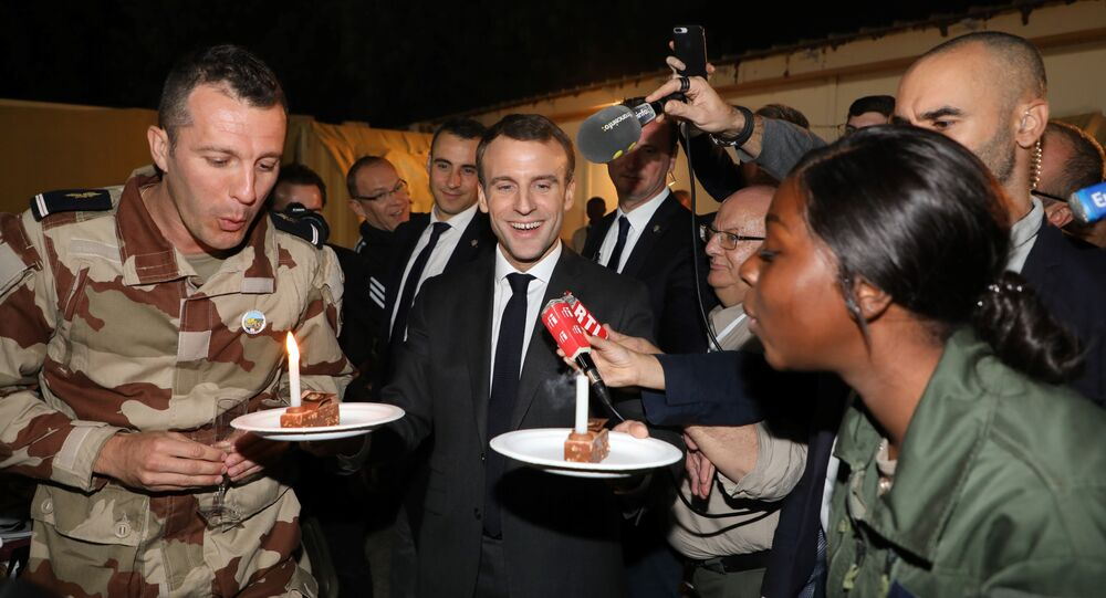 French President Emmanuel Macron celebrates the birthdays of two French soldiers including Nana (22) of Mali, from the Barkhane force during a dinner at the Barkhane tactical command center in N'Djamena on December 22, 2018.