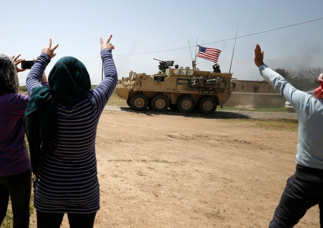 People gesture at a US military vehicle in Amuda province, northern Syria
