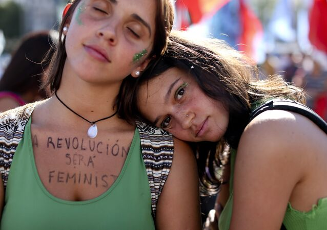 A woman wears a message on her chest that reads in Spanish: The revolution is feminist during a demonstration celebrating International Women's Day, in Buenos Aires, Argentina, Thursday, March 8, 2018