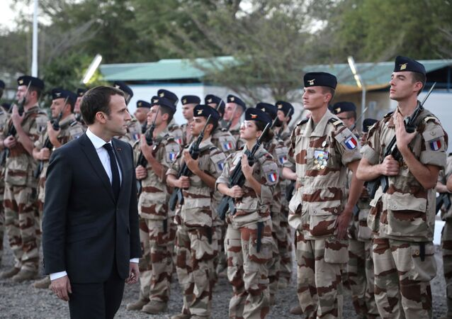 French president Emmanuel Macron reviews the troops as he arrives at the Barkhane tactical command center of the Barkhane force in N'Djamena on December 22, 2018. French president is on visit to meet with Chadian president and with soldiers from the Barkhane mission in Africa's Sahel region.