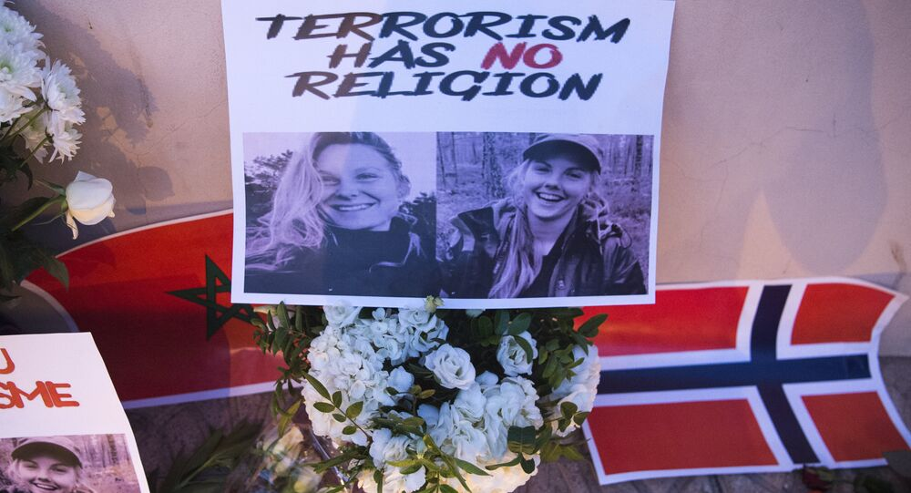 This picture taken on December 21, 2018 shows a combo photo murdered Danish student Louisa Vesterager Jespersen (L) and Nowegian Maren Ueland placed on top of flowers and between the flags of Morocco an Norway as Moroccans pay tribute to the Scandinavian victims