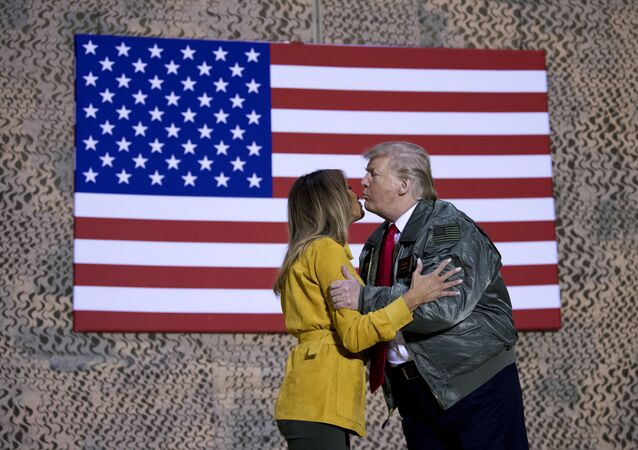 President Donald Trump kisses first lady Melania Trump during a hanger rally at Al Asad Air Base, Iraq, Wednesday, Dec. 26, 2018