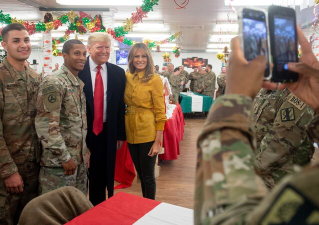 US President Donald Trump and First Lady Melania Trump take photos with members of the US military during an unannounced trip to Al Asad Air Base in Iraq on December 26, 2018