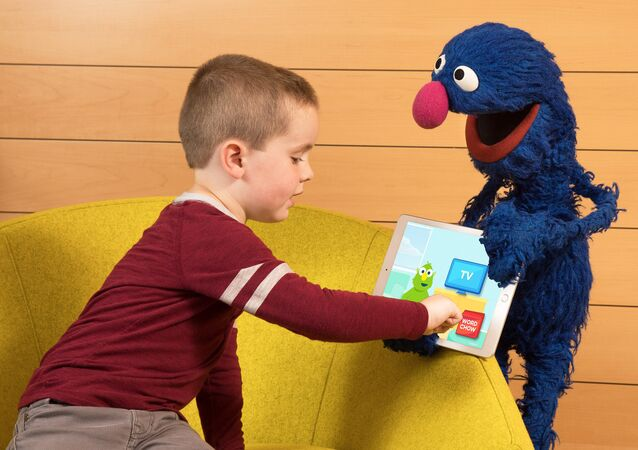 In this photo taken by Feature Photo Service for IBM: A child shows his friend Grover the new cognitive vocabulary learning app from IBM and Sesame Workshop. The app was recently piloted in Gwinnett County Public School System in Georgia to enhance students' vocabulary development.