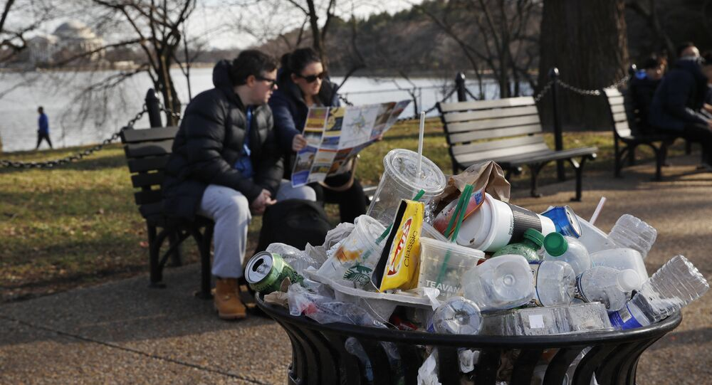 A trash can overflows as people site outside of the Martin Luther King Jr. Memorial by the Tidal Basin, Thursday, Dec. 27, 2018, in Washington, during a partial government shutdown