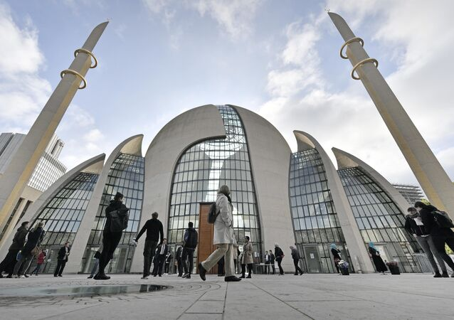 FILE - In this Oct. 3, 2017 file photo people stand outside the new central DITIB mosque on the Day of Open Mosques in Cologne. The controversial new mosque by the organization of Turkish-Islamic Union for Religious Affairs is the largest mosque in Germany