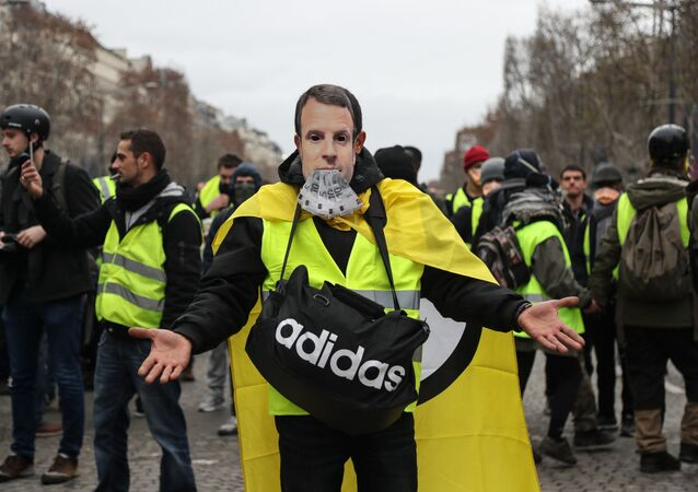 A protestor wearing a yellow vest (gilet jaune) and with a French President Emmanuel Macron mask poses on the Champs Elysees avenue in Paris on December 8, 2018 during protest against rising costs of living they blame on high taxes.